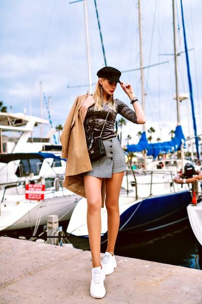 ヨット、モダンな魅力の流行の服、豪華な休暇、春秋の時間とマリーナの近くの通りでポーズの女性のファッション全長画像。路上でポーズのセクシーなモデル。 無料写真
