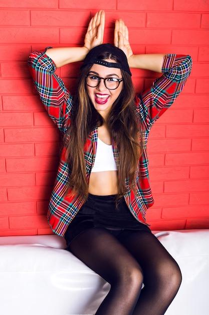Модный смешной крытый портрет молодой красивой хипстерской женщины, весело проводящей время в одиночестве на городской стене венчания, с потрясающими длинными волосами брюнетки и ярким макияжем, в очках, шляпе и клетчатой рубашке. Бесплатные Фотографии