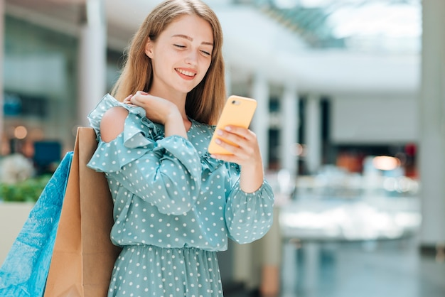Fashion girl checking phone in mall Free Photo