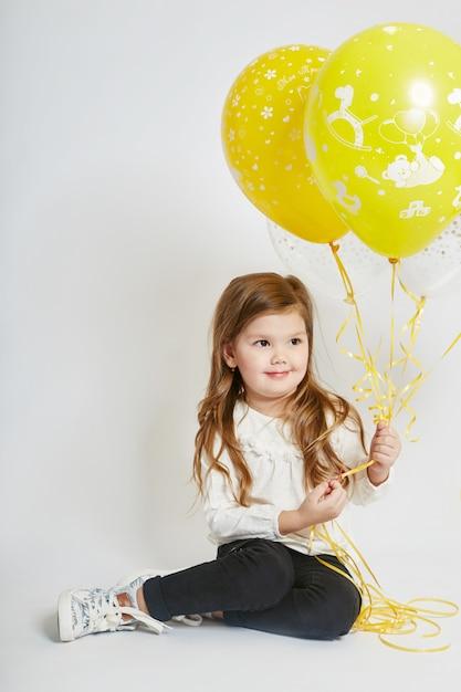 Fashion girl child celebration with balloons Premium Photo