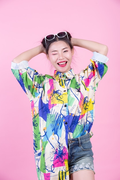 Fashion girl dress up with hand gestures on a pink background. Free Photo