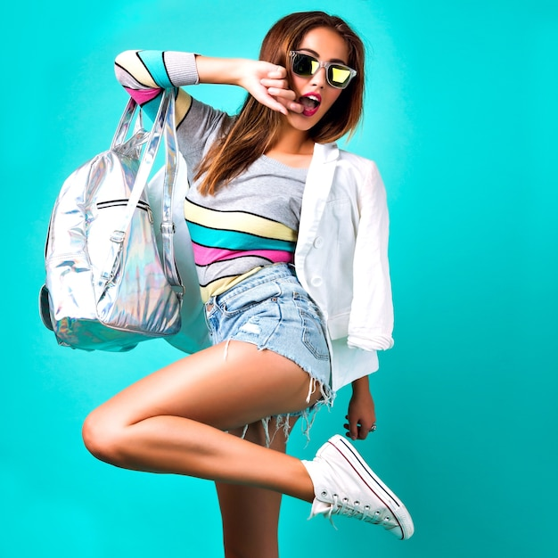 Fashion girl posing at studio, wearing smart casual sportive outfit, business style, sweet pastel colors, sunglasses, backpack denim and jacket, mint background, stylish woman. Free Photo