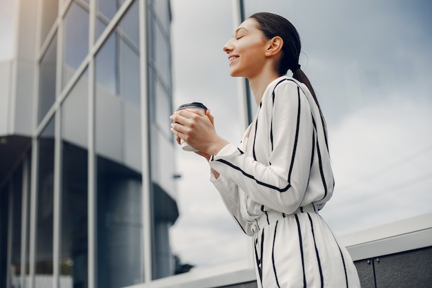 Fashion girl standing in a summer city Free Photo