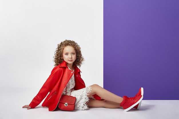 Fashion girl in stylish clothes on colored wall background. autumn bright clothes on children Premium Photo