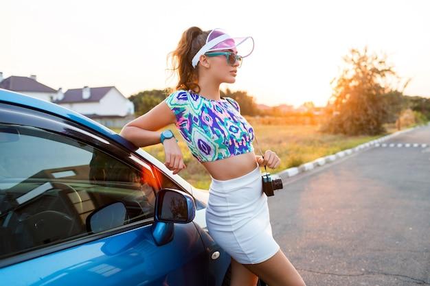 Ragazza di modo in cappuccio trasparente alla moda in posa vicino all'auto durante il viaggio Foto Gratuite