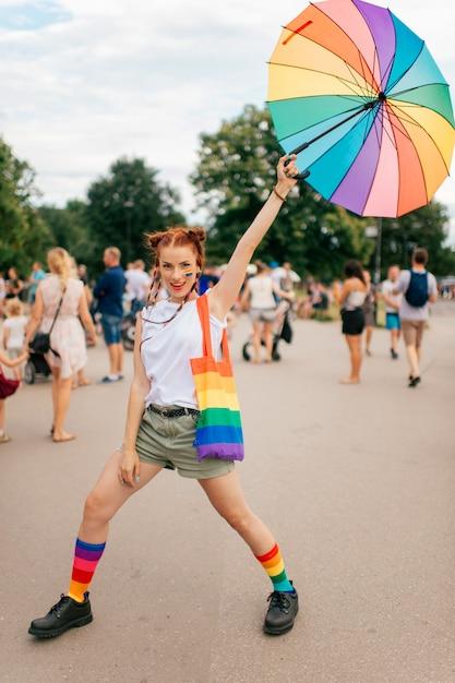 Фасонируйте девушку с флагом гей-парада lgbt на ее лице представляя с зонтиком на улице. Premium Фотографии