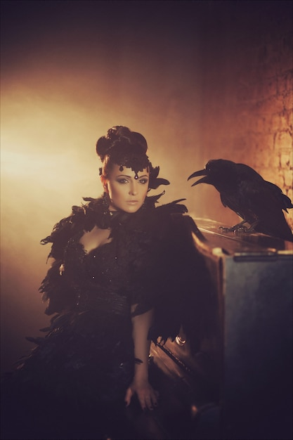 Fashion gothic portrait of a beautiful brunette with raven in a long black dress made of raven feathers. halloween Premium Photo