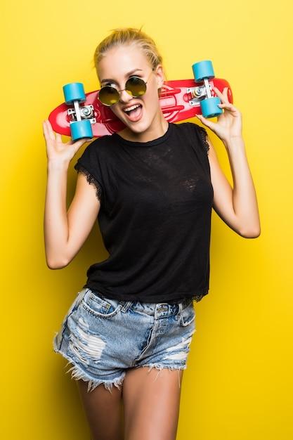 Модная счастливая улыбающаяся хипстерская крутая девушка в солнечных очках и яркой одежде со скейтбордом веселится на открытом воздухе на оранжевом фоне Бесплатные Фотографии