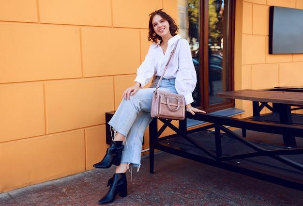スタイリッシュなカジュアルな白いブラウスとジーンズで短い髪型とかなりブルネットの少女のファッション画像。ヒールにブラックのレザーブーツ。黄色の壁のモダンなカフェの近くに座っている女の子。 無料写真