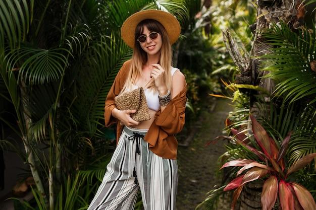 Модный образ сексуальной изящной женщины в соломенной шляпе, позирующей на тропических пальмовых листьях Бесплатные Фотографии