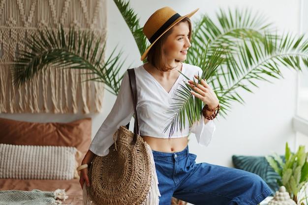 自由奔放に生きるスタイルで自宅でポーズスタイリッシュなブルネットの女性のファッション画像 無料写真