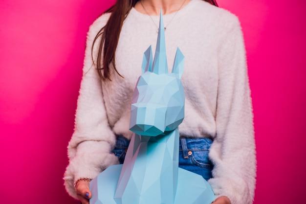 Fashion kid. designer collection. white big unicorn origami made paper. girl in beautiful pink dress. studio shot. Premium Photo