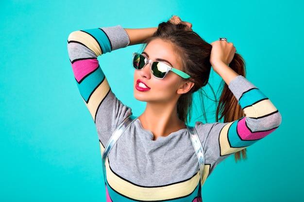 Портрет образа жизни моды радостной смешной женщины, сексуальных полных губ, зеркальных солнцезащитных очков, держа ее волосы как два хвостика, весенние цвета, мятный фон. милые эмоции, модная женщина. Бесплатные Фотографии