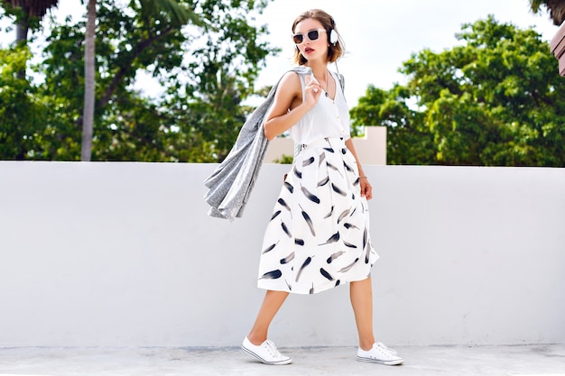 Fashion lifestyle portrait of young happy pretty woman jumping and having fun on the street at nice sunny summer day, listening favorite music at earphones,stylish vintage outfit, bright fresh colors. Free Photo