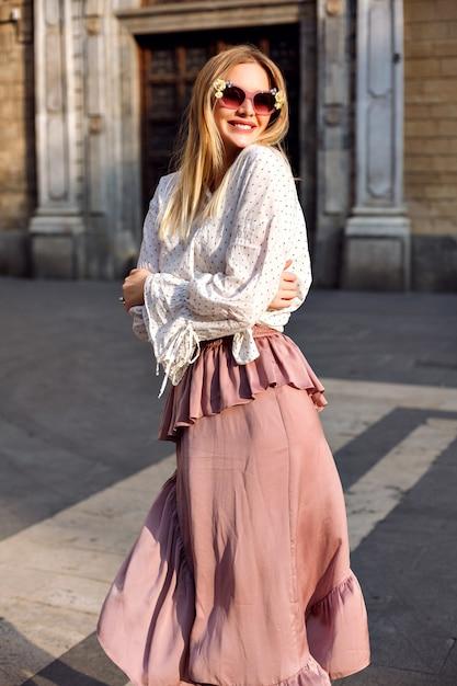 長いシルクのスカートとブラウスを身に着けている通りでポーズをとる金髪の女性のファッション高級日当たりの良い肖像画 無料写真