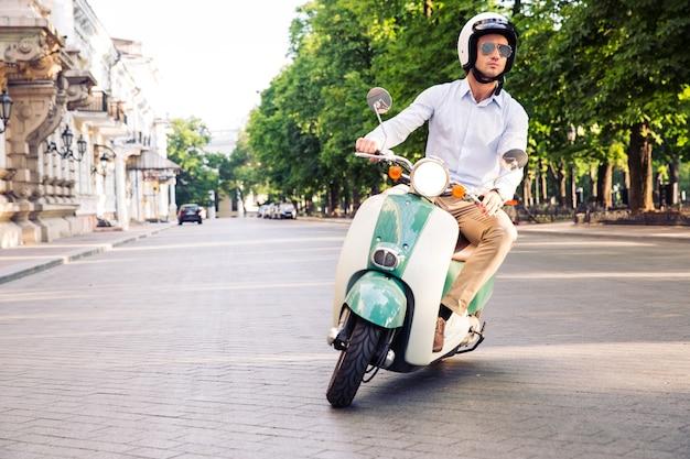 Fashion man driving a scooter Premium Photo