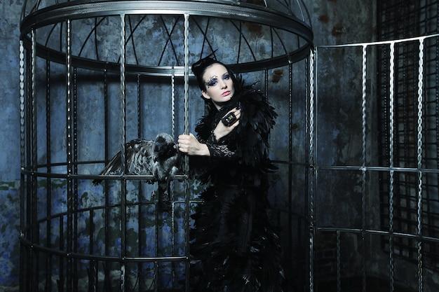 Fashion model in fantasy dress posing in steel cage. Premium Photo