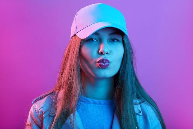 ピンクのネオン空間、丸みを帯びた唇でポーズ、長い髪の美しさスタイリッシュな女性にキスジェスチャーを作るファッションモデルの女の子 Premium写真