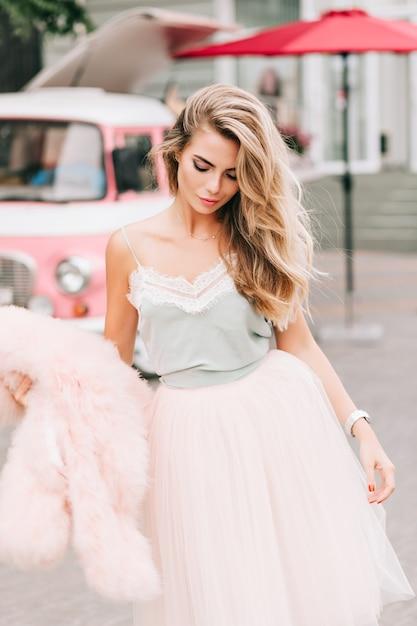 レトロな車の背景にチュールスカートのファッションモデル。彼女は長いブロンドの髪をしていて、ピンクの毛皮のコートを手に持ち、見下ろしています。 無料写真