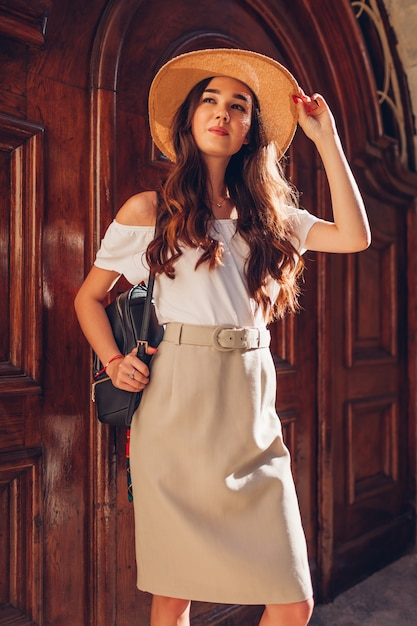 Fashion model. outdoor portrait of young beautiful woman wearing straw hat and holding backpack. Premium Photo