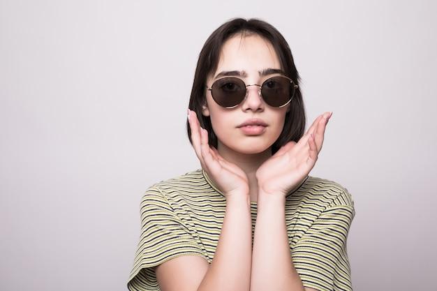 Modello di moda con i capelli corti. giovane ragazza in occhiali da sole con le mani vicino alla posa del viso Foto Gratuite