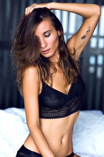 Модный утренний портрет красивой застенчивой брюнетки сексуальной женщины в роскошном гламурном нижнем белье, позирующей в одиночестве в своей спальне, будуарном стиле Бесплатные Фотографии