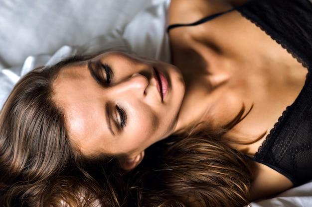 섹시 놀라운 젊은 갈색 머리 여자의 패션 아침 초상화, 침대에 누워, 란제리를 입고 휴식, 럭셔리 라이프 스타일, 자연의 아름다움, 녹색 올리브 눈, 검게 그을린 완벽한 몸. 무료 사진