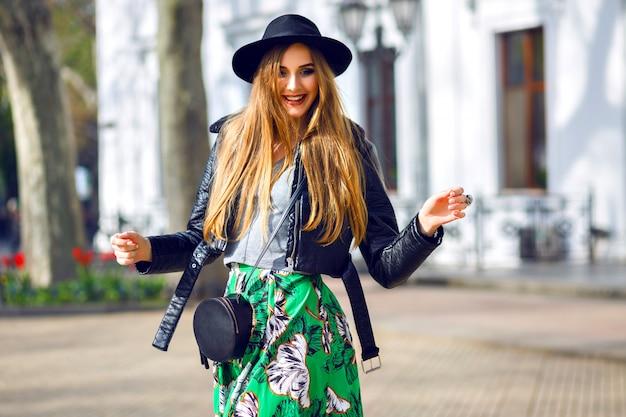 Модный открытый городской портрет стильной хипстерской женщины, идущей по улице и веселой, молодой женщины-путешественника, модницы, женской красоты, длинной винтажной юбки, ретро шляпы и байкерской куртки. Бесплатные Фотографии