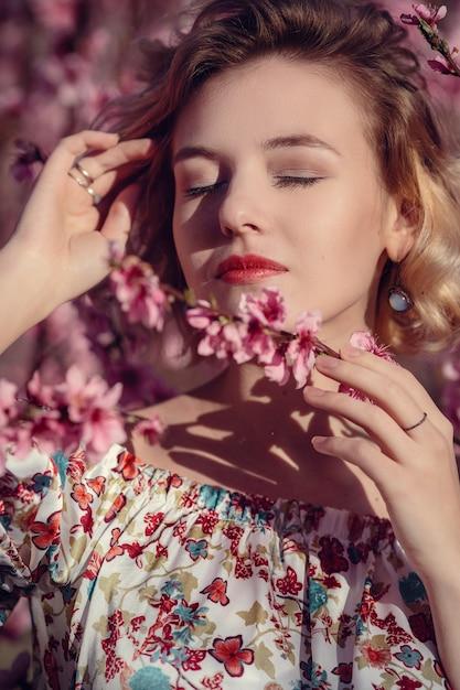 花の桃の木と庭でポーズをとってエレガントなドレスを着たゴージャスな若い女性のファッション屋外写真。花の咲く庭園で金髪 Premium写真