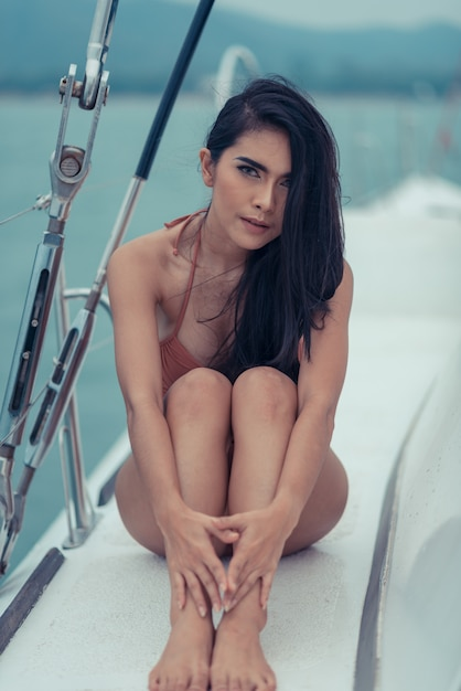 Fashion outdoor summer photo of sexy girl with dark hair in luxurious bikini relaxing on yacht in the sea Premium Photo