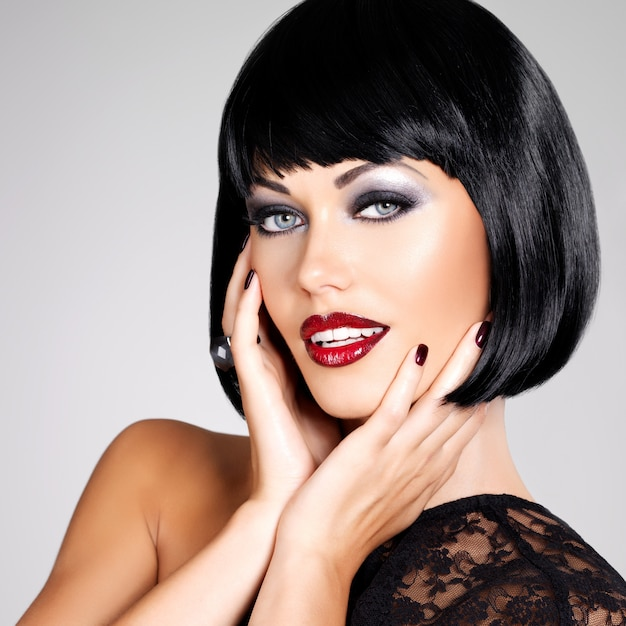 샷된 헤어 스타일으로 아름 다운 갈색 머리 여자의 패션 사진. 붉은 입술과 손톱 근접 촬영 여자의 얼굴 무료 사진