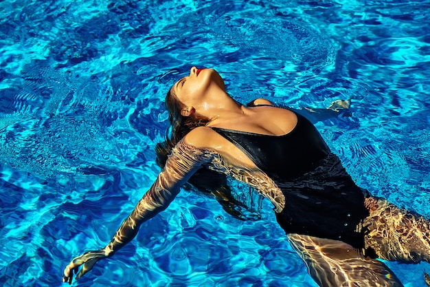 Fashion photo of sexy hot beautiful girl model with dark hair in black swimwear swimming on back in swimming pool with red lips Free Photo