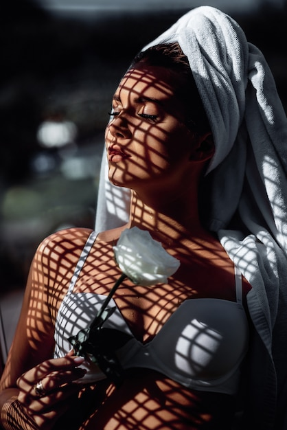 Fashion photo of young beautiful woman with closed eyes and shadows on her face. brunette with a towel on her head, in white lingerie and a white flower in her hand, poses for the camera. Premium Photo