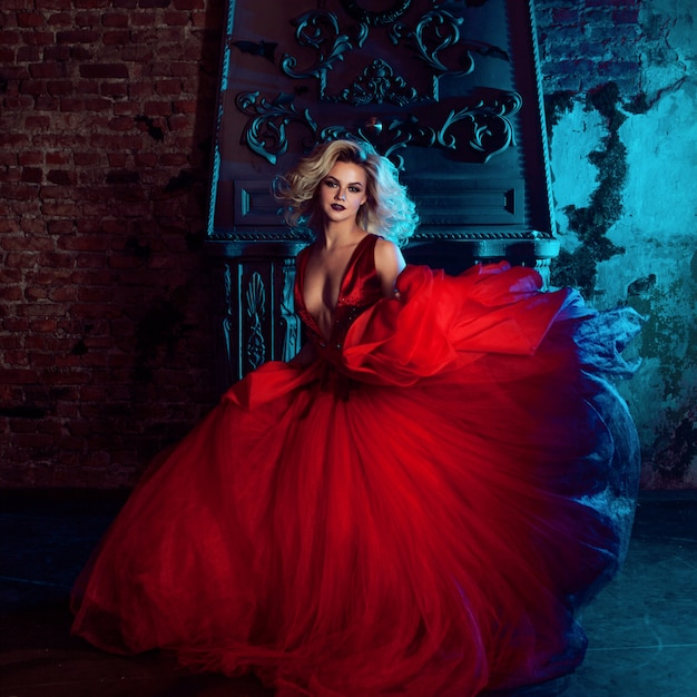 Fashion photo of young magnificent woman. running towards camera. seductive blonde in red dress with fluffy skirt Premium Photo