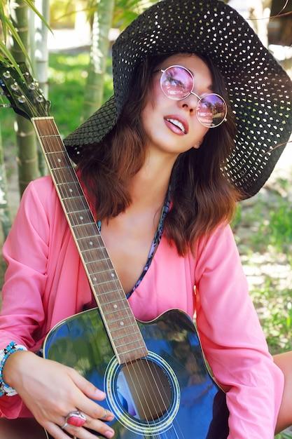Moda ritratto di bella ragazza con trucco naturale e soffici capelli castani in posa in giardino con la chitarra. indossa un cappello e occhiali da sole rosa alla moda rotondi. Foto Gratuite