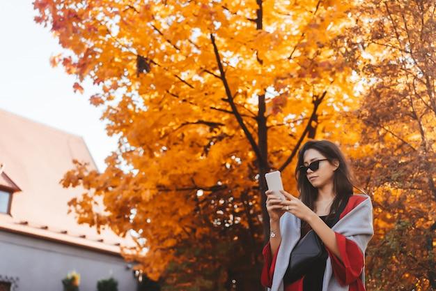 Fashion portrait of beautiful woman in autumn park Free Photo