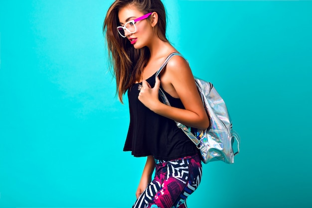 Fashion portrait of beautiful woman, tanned perfect skiing bright make up, trendy sportive outfit, printed leggings, silver backpack Free Photo