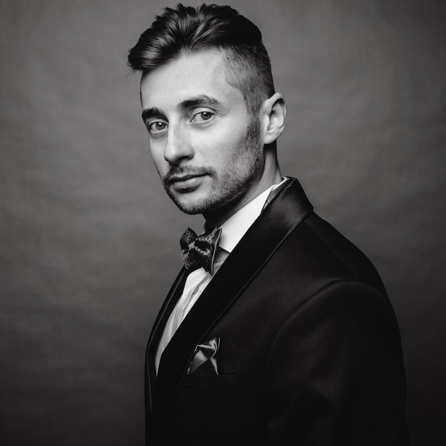 Fashion portrait of handsome elegant man with curly hair wearing tuxedo posing on gray background in studio. black and white photo Premium Photo