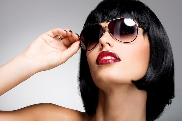 빨간 선글라스와 샷된 헤어 스타일을 가진 아름 다운 갈색 머리 여자의 패션 초상화 무료 사진