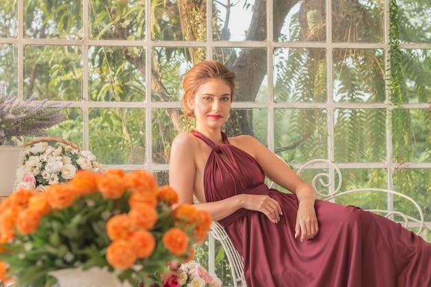 Мода портрет красивая женщина в саду стекла дом с платьем. Premium Фотографии