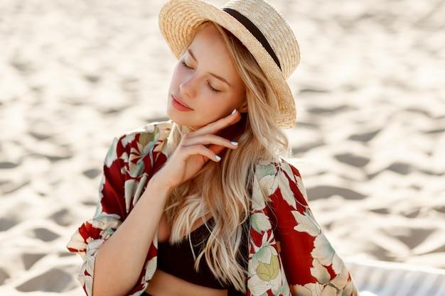 太陽が降り注ぐビーチで休んでいる自然なメイクでゴージャスな金髪の女性のファッションの肖像画。麦わら帽子をかぶっています。休日と休暇の気分。 無料写真