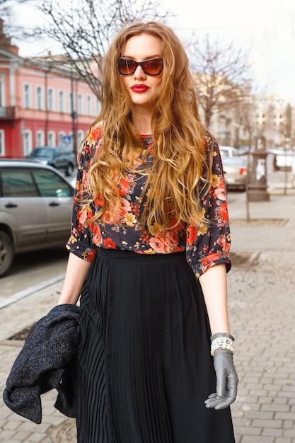 古いヨーロッパの都市の町の通りを一人で歩いて、レトロなエレガントな服とサングラスを着て楽しんで、かなりスタイリッシュな若い女性のファッションの肖像画。ヴィンテージの秋スタイル。 無料写真