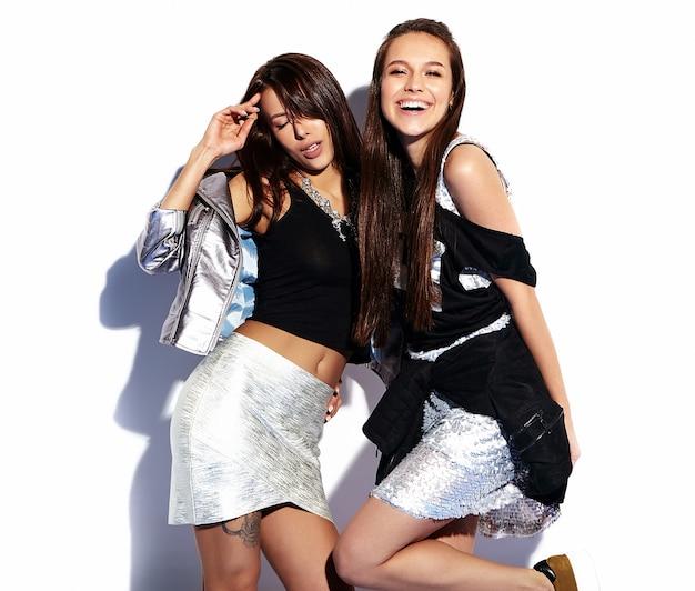 Портрет двух улыбающихся брюнеток в летней повседневной хипстерской одежде на белом Бесплатные Фотографии