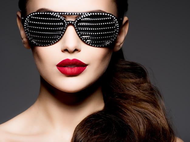 다이아몬드와 붉은 입술과 검은 선글라스를 착용하는 여자의 패션 초상화 무료 사진