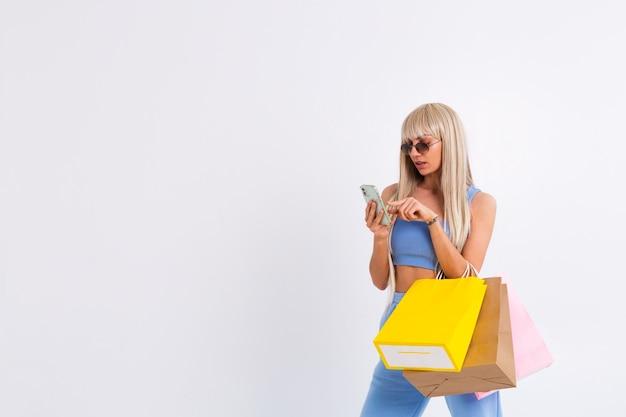 긴 화려한 스트레이트 헤어를 가진 젊은 금발의 여자의 패션 초상화 잡고 다채로운 쇼핑 가방 무료 사진