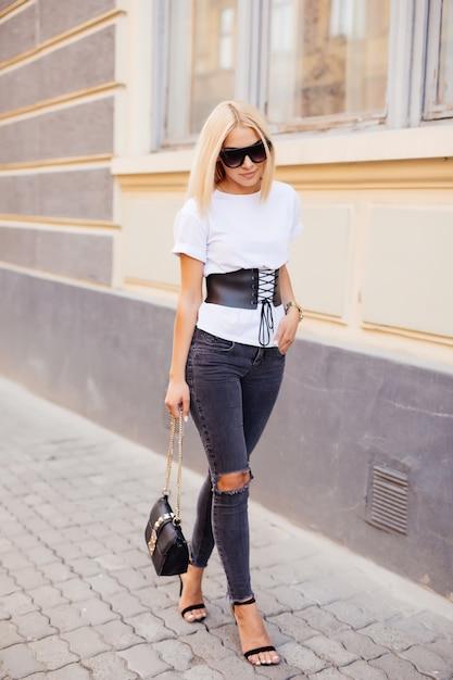 Портрет моды молодой элегантной белокурой женщины внешней. серое платье, кожаный рюкзак, солнцезащитные очки Бесплатные Фотографии