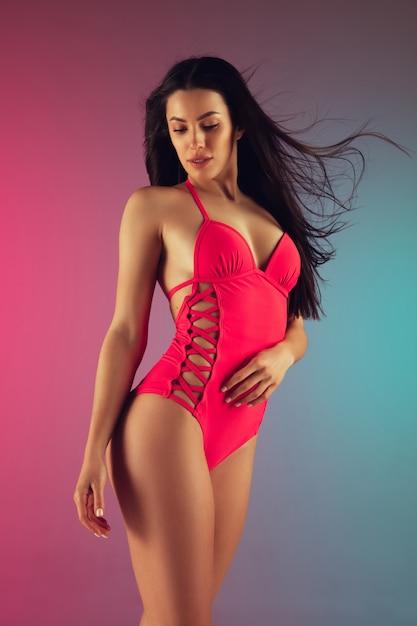 グラデーションのスタイリッシュなピンクの高級水着で若いフィットと陽気な女性のファッションの肖像画。夏にぴったりのパーフェクトボディ。 無料写真