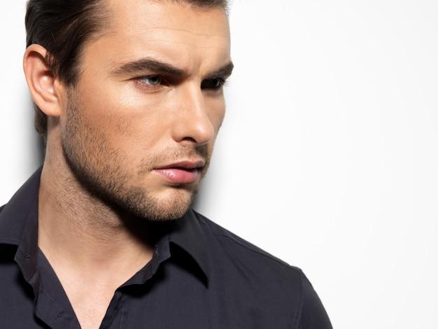 黒のシャツを着た若い男のファッションの肖像画は、コントラストの影で壁を越えてポーズをとる 無料写真