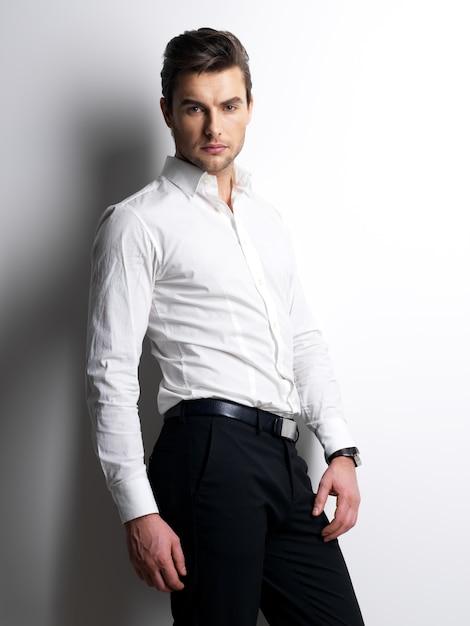 白いシャツを着た若い男のファッションの肖像画は、コントラストの影で壁を越えてポーズをとる 無料写真