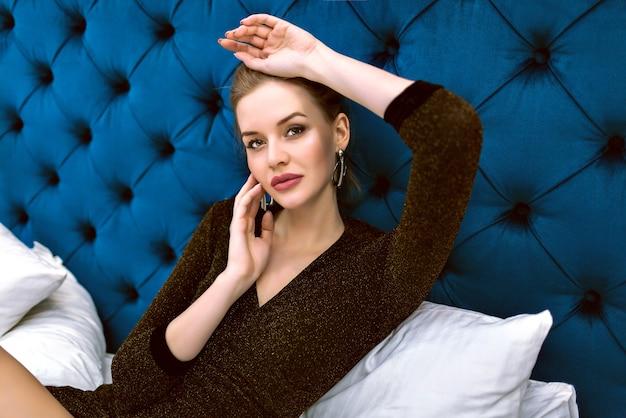 高級ホテルでポーズをとって、ベッドの上に敷設、柔らかいトーンの色のイブニングトレンディなドレスとジュエリーを身に着けている官能的なエレガントな女性のファッションの肖像画。 無料写真